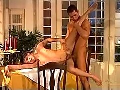 Two young waiters having fun right on dinner table