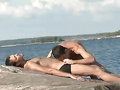 Sexy gay greedily gorges cock on island