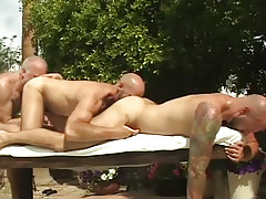 Three mature bears kiss each other by pool