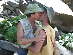 Gay fisherman kisses mate by river